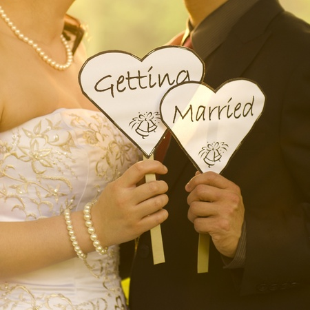 getting together: Outdoor Bride and Groom holding getting married sign Stock Photo