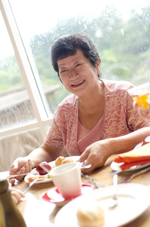 Asian senior woman enjoying her dining with family in a restaurant photo