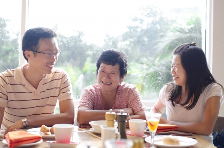 candid: Asian young adults and senior having good time in restaurant Stock Photo