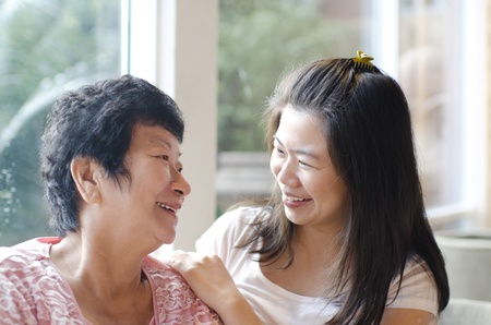 conversations: Asian family, adult daughter having conversation with senior mother indoor.