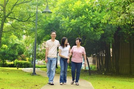 ancianos caminando: Adultos de Asia con una caminata al aire libre con la madre de alto