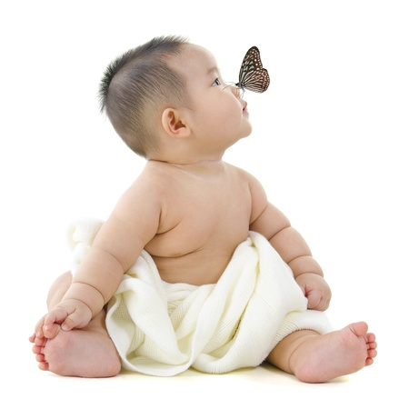 surprised baby: Butterfly flying to Asian baby boy nose, on white background Stock Photo