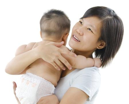 pampering: Pan Asian madre mimar a su beb� en el fondo blanco