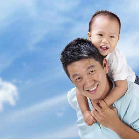 piggy back: Outdoor Asian family over blue sky