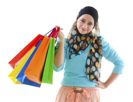 年輕漂亮的穆斯林婦女拿著購物袋