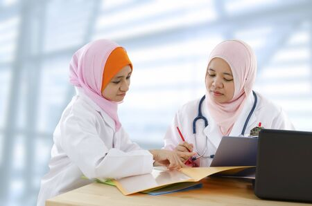 Two Muslim female doctor discussing patient report photo