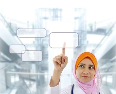 Young Muslim female doctor finger pressing on touchscreen monitor button, modern building background photo
