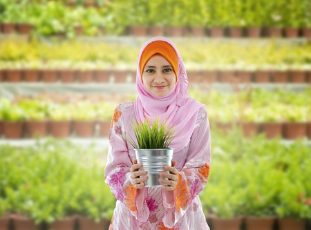 Concept of young Muslim girl holding a plant on nursery photo