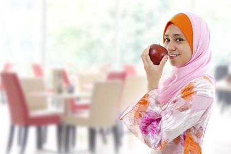 mujeres musulmanas: Mujer musulmana joven comer manzana, el concepto de alimentaci�n saludable