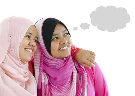 Two Muslim women having thought together, looking at side photo