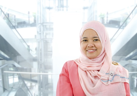 Asian Muslim woman standing on modern office background photo