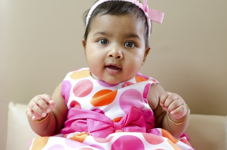 Adorable 6 months old Indian baby girl sitting on sofa photo