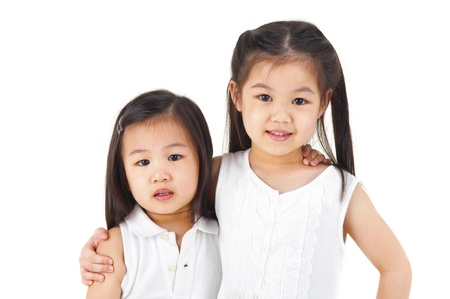 two girls hugging: Asian sisters arms around on plain background Stock Photo