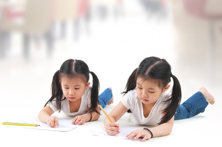 writing activity: Little Asian girls drawing, lying on floor