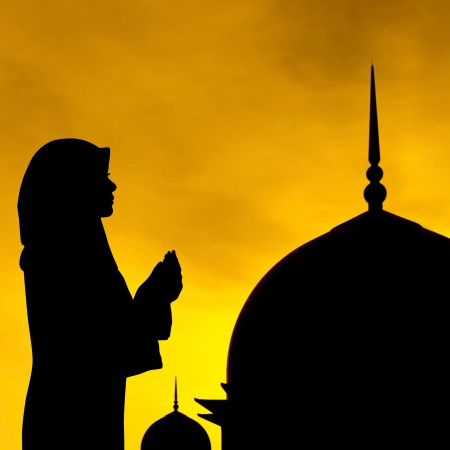 Silhouette of prayer and mosque in sunset. photo