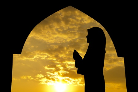 personas orando: Silueta de Mujer musulmana rezando en la mezquita durante el tiempo de puesta de sol Foto de archivo