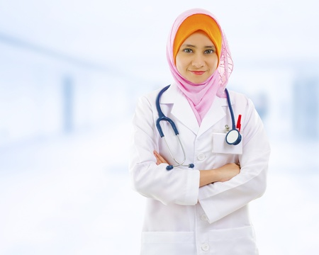 muslimah: Confident Muslim female doctor standing inside hospital