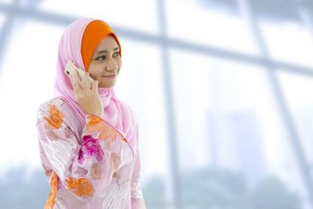 femmes muslim: Femme d'affaires musulman au t�l�phone, en regardant sur le c�t�. Banque d'images