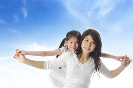 亞洲快樂的母親背著女兒在藍色的天空
