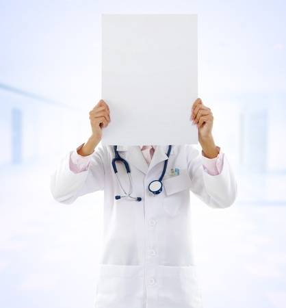 medical student: Mixed race female doctor showing blank board on hospital background