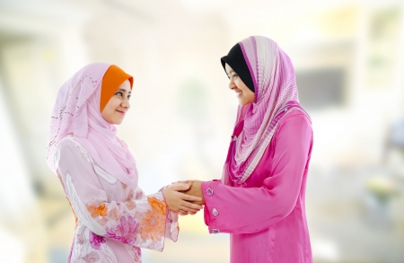 malay ethnicity: Muslim woman in traditional clothing greeting to each other, indoor. Stock Photo