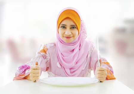 Muslim an and empty food for fork holding inside knife plate ready restaurant with woman  photo