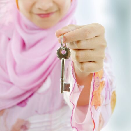 Muslim woman hand holding a new key photo