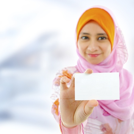 Muslim female holding business card, focus on hand photo
