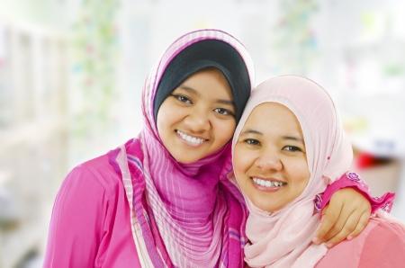 mujeres musulmanas: Felices las mujeres musulmanas en pie dentro de la casa