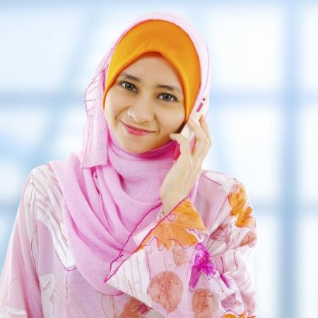 fille arabe: Femme d'affaires musulman sur le t�l�phone, en regardant � c�t�.