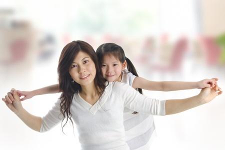Happy Asian mother piggyback ride daughter indoor photo