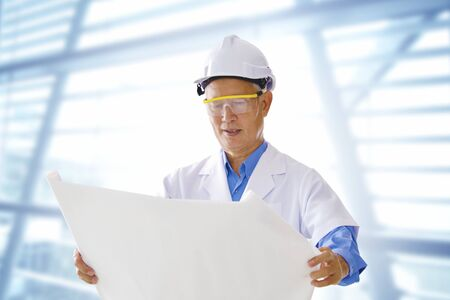 Senior Asian engineer with blueprints office background Stock Photo - 13736870