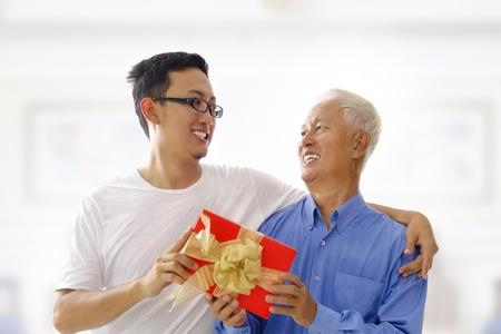 Gelukkig gemengd ras Aziatische vader ontvangt cadeau van zijn zoon Stockfoto