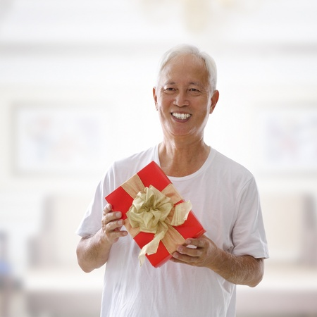 Happy mixed race Senior Asian man holding a gift box and smiling photo