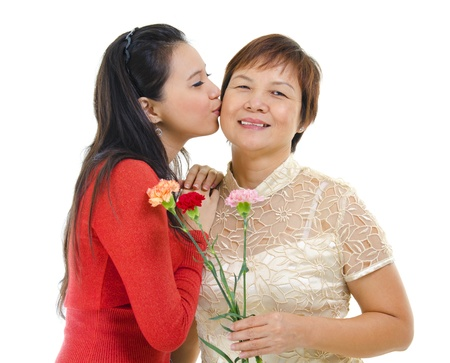Mixed race asian daughter giving a kiss to her mum isolated on white photo