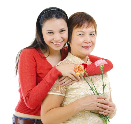 Asian mother holding carnation flower with her daughter isolated on white background photo
