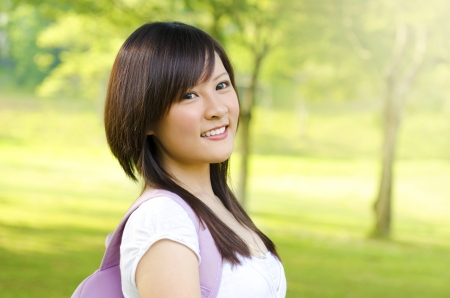 Asian adult student standing outdoor park, green tree background photo