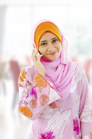 Muslim young woman on the phone, looking at camera. photo