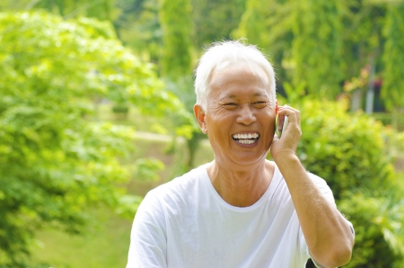 Healthy senior Asian man on the phone outdoor green park photo