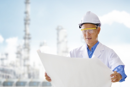 Senior Asian engineer with blueprints standing outside plant photo