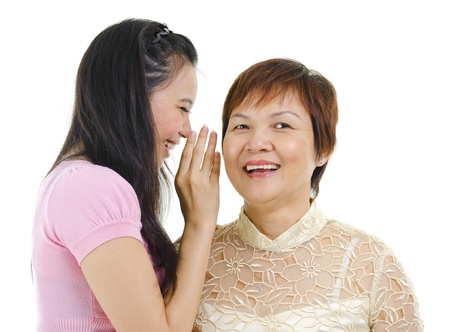 Young Asian daughter talking secretly to her mum photo