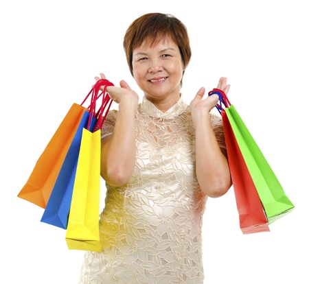 Happy mature Asian shopper holding shopping bag isolated on white background photo