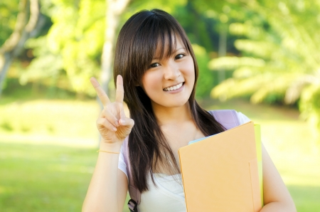 Cute teen with victory sign standing photo