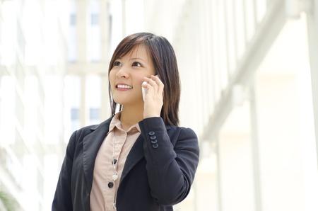 llamando: Empresaria asiática caminar en la calle que pasa por un edificio de oficinas.