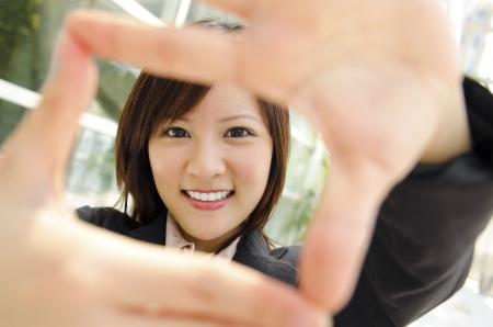 objetivo: Sonriente mujer de negocios asiática hacer un marco con los dedos
