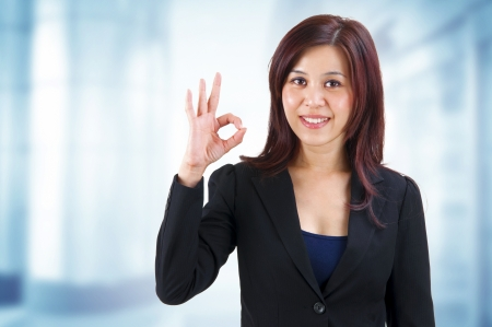 okay: Mixed race Mid Adult Asian showing ok hand sign in work place