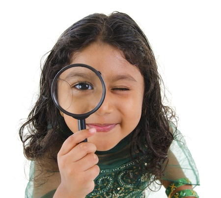 A little Indian girl peers at the camera through a magnifying glass, isolated on white background photo