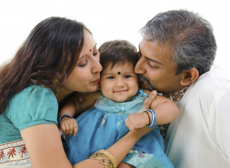 bonding: Indian parents giving their daughter a kiss, isolated on white background Stock Photo