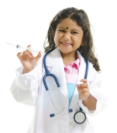 Cute little Indian future doctor holding syringe with cheerful smile isolated on white background Stock Photo