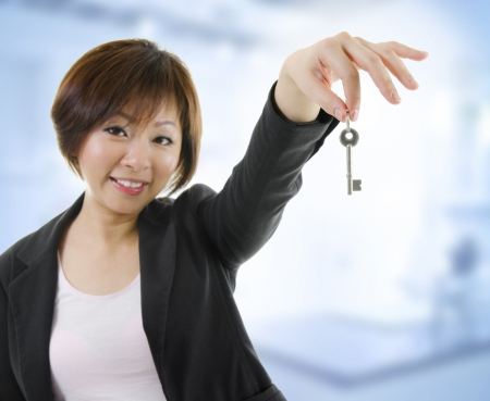 Mid adult Asian woman arms out holding a new key photo